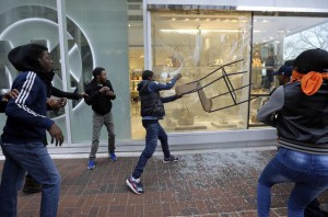 A protestor breaks a window at a store after a rally for Freddie Gray, Saturday, April 25, 2015, in Baltimore. Gray died from spinal injuries about a week after he was arrested and transported in a police van. (ANSA/AP Photo/Patrick Semansky)
