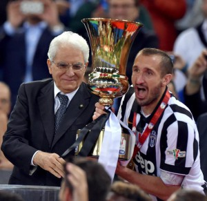 Italian President Sergio Mattarella hands the trophy to Juventus's player Giorgio Chiellini after winning the Italy Cup