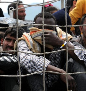 Migrants wait to disembark from the Irish naval ship Le Eithne