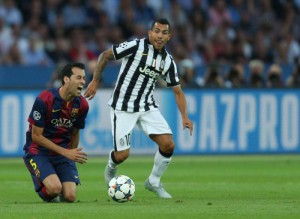 Barcelona's Sergio Busquets (L) and Carlos Tevez of Juventus