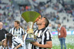 Juventus' Carlos Tevez celebrates with the trophy of Italian Serie A