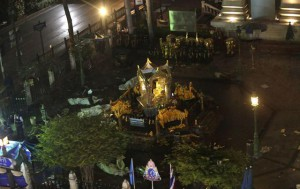 A general view taken from a moving train shows bodies covered in white sheets around the Erawan Shrine, central Bangkok, Thailand, 17 August 2015. EPA/BARBARA WALTON
