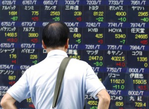 A man looks at an electronic stock indicator of a securities firm in Tokyo, Tuesday, Aug. 11, 2015. (ANSA/AP Photo/Ken Aragaki)