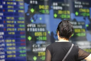 A woman looks at an electronic stock indicator of a securities firm in Tokyo, Tuesday, July 28, 2015. (ANSA/AP Photo/Shizuo Kambayashi)