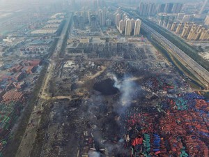 An aerial view of a large hole in the ground in the aftermath of a huge explosion that rocked the port city of Tianjin, China, 15 August 2015. EPA/STR CHINA OUT