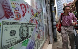 A file photo dated 13 September 2010 showing a man walking past oversized Chinese yuan (RMB) notes, US bank notes and other foreign currency seen out side a foreign exchange in Hong Kong, China. China's central bank on 12 August 2015 devalued the yuan for the second time in two days, to aid a slowing economy. EPA/YM YIK
