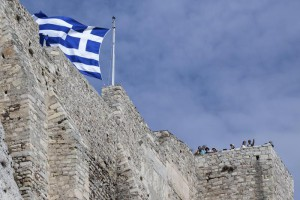 A Greek flag flutters next to visitors overlooking the city from the Acropolis hill in Athens, Greece, Friday, Aug. 14, 2015. (ANSA/AP Photo/Giannis Papanikos)