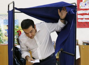 Greek Prime Minister Alexis Tsipras (C) casts his ballot in a voting centre during a referendum in Athens, Greece, 05 July 2015.  ANSA/ARMANDO BABANI