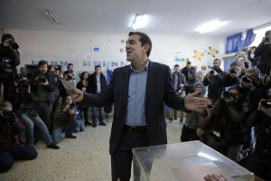 Alexis Tsipras, leader of Greece's Syriza left-wing main opposition party surrounded by photographers reacts as he casts his vote at a polling station in Athens, Sunday, Jan. 25, 2015. (ANSA/AP Photo/Lefteris Pitarakis)