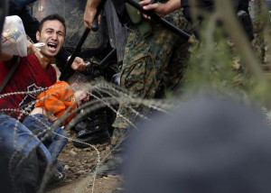 CORRECTS THE LOCATION A migrant man holding a boy react as they are stuck between Macedonian riot police officers and migrants during a clash near the border train station of Idomeni, northern Greece, Friday, Aug. 21, 2015. (ANSA/AP Photo/Darko Vojinovic)