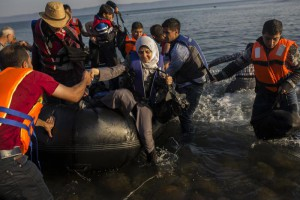 Migrants from Syria and Afghanistan arrive on an overcrowded dinghy from the Turkish coasts to the Greek island of Lesbos, Monday, July 27, 2015. (ANSA/AP Photo/Santi Palacios)