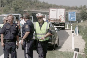 Police stand in front of a truck parked on the shoulder of the highway A4 near Parndorf south of Vienna, Austria, Thursday, Aug 27, 2015. At least 20 migrants were found dead in the truck parked on the Austrian highway leading from the Hungarian border, police said. (ANSA/AP Photo/Ronald Zak)