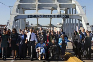 """President Barack Obama, fourth from left, walks holding hands with Amelia Boynton Robinson, who was beaten during """"Bloody Sunday,"""" as they and the first family and others including Rep. John Lewis, D-Ga, left of Obama, walk across the Edmund Pettus Bridge in Selma, Ala,. (ANSA/AP Photo/Jacquelyn Martin)"""
