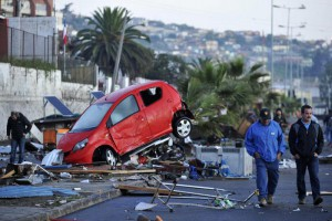 Chileans pass a wrecked car pushed by strong waves, after a magnitude 8.4 Richter scale earthquake, in Coquimbo, Chile, 17 September 2015. EPA/ALEJANDRO PIZARRO CHILE OUT