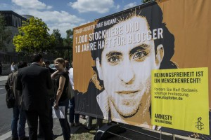 Protesters stand in front of a placard reading '1,000 lashes and 10 years of prison for a blogger' and 'Freedom of speech is a human right' which they placed in front of the Saudi-Arabian embassy in Berlin,??Germany, 22??May 2015.     ANSA/PAUL ZINKEN