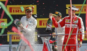 Mercedes driver Lewis Hamilton, left, winner, sprays champagne on the podium flanked by second placed Ferrari driver Sebastian Vettel, of Germany, and third placed Felipe Massa, of Brazil, during the podium ceremony for the Formula One Italian Grand Prix, at the Monza racetrack, Italy, Sunday, Sept. 6, 2015. (ANSA/AP Photo/Luca Bruno)