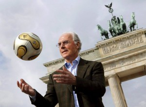 World Cup organising committee chief Franz Beckenbauer showcases the golden football developed especially for the final of the upcoming World Cup in front of Berlin's Brandenburg Gate, Germany Tuesday 18 April 2006.  ANSA/PEER GRIMM