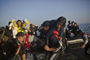 Refugees rush to the beach as they arrive on a dinghy from the Turkish coast to the northeastern Greek island of Lesbos, Monday, Oct. 5, 2015. (ANSA/AP Photo/Muhammed Muheisen)