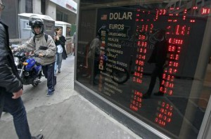 People pass an electronic monitor with currency exchange rates the Buenos Aires Stock Market in downtown Buenos Aires, Argentina, 01 August 2014. EPA/DAVID FERNANDEZ