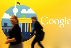 A file photo dated 26 September 2012 showing women walking past the company logo in the offices of the subsidiary of Google in Berlin, Germany. Trading in Google shares was halted in New York after company results were made public before the closing bell, 18 October 2012. EPA/BRITTA PEDERSEN