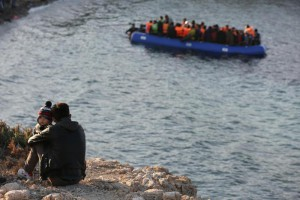 A migrant and a child watches a dinghy of people travel from the Turkish coast to the Greek island of Chios, near Cesme, Turkey, Monday, Nov. 9, 2015. (ANSA/AP Photo/Emre Tazegul)