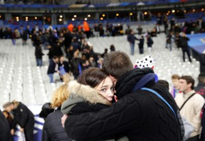 Spectators embrace each other as they stand on the playing field of the Stade de France stadium at the end of a friendly soccer match between France and Germany in Saint Denis, outside Paris, Friday, Nov. 13, 2015. (AP Photo/Christophe Ena)