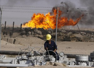 FILE - In this Dec. 13, 2009 file photo, an Iraqi worker operates valves at the Rumaila oil refinery near the city of Basra, 550 kilometers (340 miles) southeast of Baghdad, Iraq.  (AP Photo/Nabil al-Jurani, File)