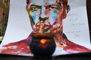 A candle sits in front of a painting of David Bowie at a mural of the British singer in Brixton, birth place of the late David Bowie in London, Britain, 11 January 2016.   EPA/ANDY RAIN