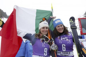 Italy's Nadia Franchini, winner, left, and Daniela Merighetti, second placed, hold an Italian flag as they celebrate at the end of a women's Alpine ski downhill race, in La Thuile, Italy, Saturday, Feb. 20, 2016. (ANSA/AP Photo/Alessandro Trovati)