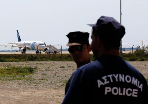 Cypriot police patrols outside a fence behind which the hijacked EgyptAir A320 plane stands parked at a sealed off area of the Larnaca Airport, in Larnaca, Cyprus, 29 March 2016. EPA/KATIA CHRISTODOULOU