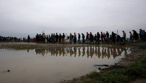 Migrants cast their reflection in a muddy puddle, while waiting in line for tea and bread in a makeshift camp at the northern Greek border post of Idomeni, Wednesday, March 16, 2016. Hundreds of migrants and refugees walked out Monday of an overcrowded camp on the Greek-Macedonian border, determined to use a dangerous crossing to head north but were returned to Greece. (ANSA/AP Photo/Boris Grdanoski)