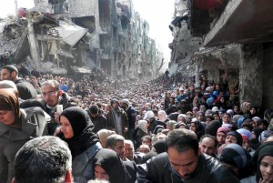 FILE - In this Jan. 31, 2014 file photo released by the United Nations Relief and Works Agency for Palestine Refugees in the Near East (UNRWA), shows residents of the besieged Palestinian camp of Yarmouk, queuing to receive food supplies, in Damascus, Syria. That year, the U.N. was able to deliver food to about five percent of people in besieged areas including Yarmouk, while today estimates show the organization is reaching less than one percent.(UNRWA via AP, File)