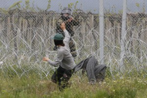 A migrant man trying to remove barbed wire along the fence clashes with Macedonian police at the northern Greek border point of Idomeni, Greece, Wednesday, April 13, 2016. New clashes have broken out between Macedonian police and stranded refugees and other migrants trying to scale a fence on Greece's border with the country. (ANSA/AP Photo/Amel Emric)