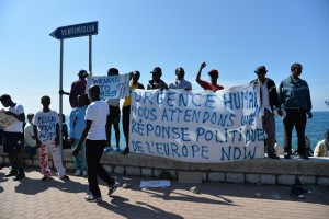Migrants protest along the sea front at the border between Italy and France