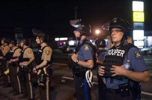 Officers from the Missouri State Highway Patrol and St. Louis County Police, wearing riot gear, guard the perimeter of the scene of an officer-involved shooting on West Florissant Avenue in Ferguson, Missouri, USA, 10 August 2015.  EPA/SID HASTINGS
