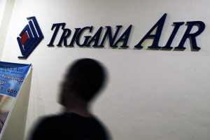 A Trigana Air employee walks passes the logo of Trigana Air at the main office, in Jakarta, Indonesia, 16 August 2015. EPA/MAST IRHAM