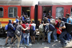 Migrants push each other to board a train that will take them to the border with Serbia, at the railway station in the southern Macedonian town of Gevgelija, on Saturday, Aug. 15, 2015. (ANSA/AP Photo/Boris Grdanoski)