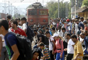 Migrants cross the raiway tracks in front of a train entering the railway station in the southern Macedonian town of Gevgelija, on Saturday, Aug. 15, 2015. (ANSA/AP Photo/Boris Grdanoski)