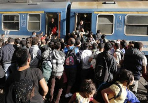 Migrants try to board a train at the railway station in Budapest, Hungary, Thursday, Sept. 3, 2015. (ANSA/AP Photo/Frank Augstein)