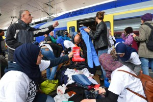 Refugees receive new clothes as they arrive at the Hauptbahnhof station in Salzburg, Austria, Saturday, Sept. 5, 2015 on their way from Hungary via Vienna to Germany. (ANSA/AP Photo/ Kerstin Joensson)