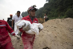 A fireman carries the body of a child recovered from the site of a landslide in Cambray, a neighborhood in the suburb of Santa Catarina Pinula, about 10 miles east of Guatemala City, Friday, Oct. 2, 2015. (ANSA/AP Photo/Moises Castillo)