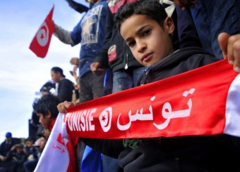 A young boy holds a scarf with Arabic inscription reading Tunisia during a demonstration against the visit of Tunisian President Moncef Marzouki on the second anniversary of the Tunisian revolution, in Sidi Bouzid, south Tunisia, 17 December 2012.  ANSA/STR