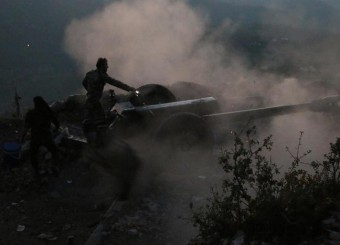 In this photo taken on Saturday, Oct. 10, 2015, Syrian army personnel operate a cannon in Latakia province, about 12 from the border with Turkey in Syria. Backed by Russian airstrikes, the Syrian army has launched an offensive in central and northwestern regions. (Alexander Kots/Komsomolskaya Pravda via AP)