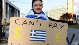 A Protestor holds a placard with a Greek flag during a demonstration outside of an EU summit in Brussels on Sunday, Oct. 23, 2011. (AP Photo/Geert Vanden Wijngaert)