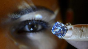 A Sotheby's employee displays the rare Blue Moon Diamond during a preview at the Sotheby's, in Geneva, Switzerland, 04 November 2015. EPA/MARTIAL TREZZINI