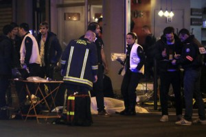 Police officers and rescue workers gather around a victim outside a Paris restaurant, Friday, Nov. 13, 2015. (ANSA/AP Photo/Thibault Camus)