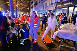 People rest on a bench after being evacuated from the Bataclan theater after a shooting in Paris, Saturday, Nov. 14, 2015. (ANSA/AP Photo/Thibault Camus)