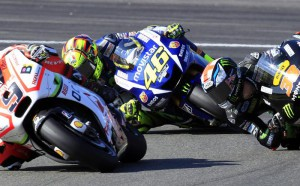 MotoGP rider Valentino Rossi of Italy steers his motorcycle between Danilo Petrucci of Italy, left, and Bradley Smith of Britain, right, during the Valencia Motorcycle Grand Prix, the last race of the season, at the Ricardo Tormo circuit in Cheste near Valencia, Spain, Sunday, Nov. 8, 2015. (ANSA/AP Photo/Alberto Saiz)