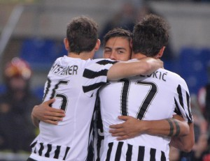Juventus' Paulo Dybala (C) jubilates with his teammates Mario Mandzukic (R) and Stephan Lichtsteiner after Lazio's Santiago Gentiletti scored the own goal during the Italian Serie A soccer match SS Lazio vs Juventus FC at Olimpico stadium in Rome, Italy, 04 December 2015. ANSA/MAURIZIO BRAMBATTI