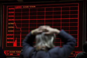 A woman reacts near a display board showing the plunge in the Shanghai Composite Index at a brokerage in Beijing, China, Thursday, Jan. 7, 2016. (ANSA/AP Photo/Ng Han Guan)
